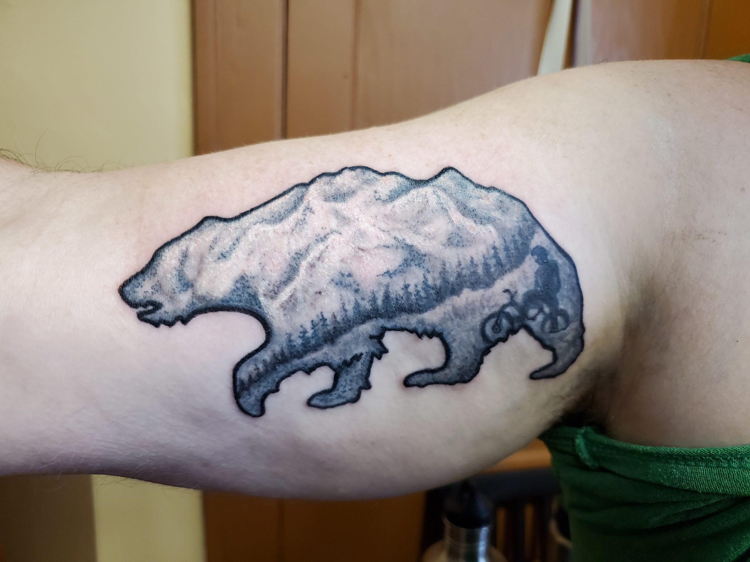 tattoo of bear image with black and gray style mountains and trees
